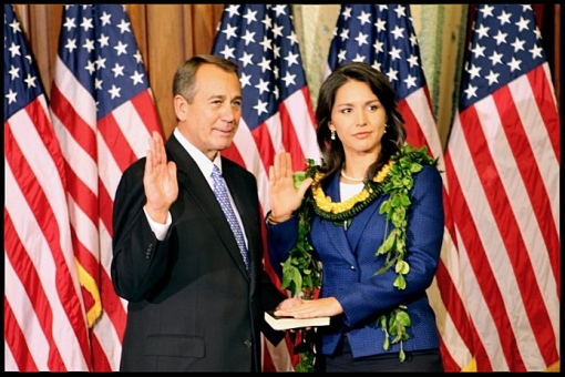 Representative Tulsi Gabbard, the first Hindu in US Congress, participates in a ceremonial swearing-in administered by Speaker of the House Rep. John Boehner.