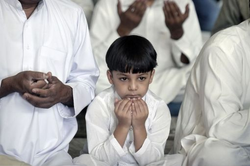 A Muslim boy prays at the start of Eid al-Fitr at the Peace and Friendship stadium in Piraeus near Athens on August 19, 2012. (Louisa Gouliamaki - AFP/Getty Images)
