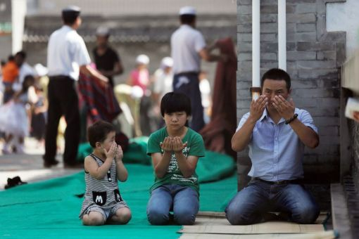 A Muslim family prays on the first day of Eid al-Fitr at Niu Jie Mosque to celebrate Eid al-Fitr on August 19, 2012 in Beijing, China. (Lintao Zhang - AFP/Getty Images)