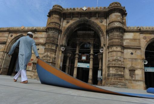 An Indian Muslim caretaker removes carpet after Eid-al-Fitr prayers at the Shahi Jama Masjid Mosque in the Walled City of Ahmedabad on August 20, 2012. (Sam Panthaky - AFP/Getty Images)