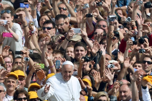 Pope Francis (C) salutes the crowd as he arrives for his general audience in St Peter's square at the Vatican on May 22, 2013. AFP PHOTO by GABRIEL BOUYS/AFP/Getty Images.