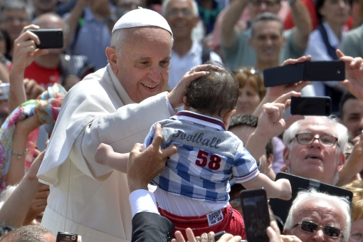 Pope Francis blesses a child as he leaves in his papamobile after the Holy mass with the ecclesial movements for Pentecost Sunday on May 19, 2013 at St peter's square at the Vatican. Photo by ANDREAS SOLARO/AFP/Getty Images.