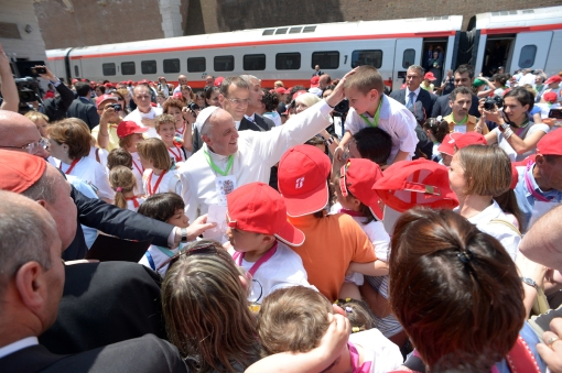 "In this photo made available by the Vatican newspaper L'Osservatore Romano, Pope Francis welcomes a group of children who traveled on a special train from Milan and arrived at the St. Peter station at the Vatican, Sunday, June 23, 2013, to meet with the Pope. During the traditional Angelus blessing, one of the most cherished traditions of the Catholic Church, the pope spoke off the cuff, telling young people in the square to not be afraid of ""going against the current."" Photo by Associated Press/L'Osservatore Romano."