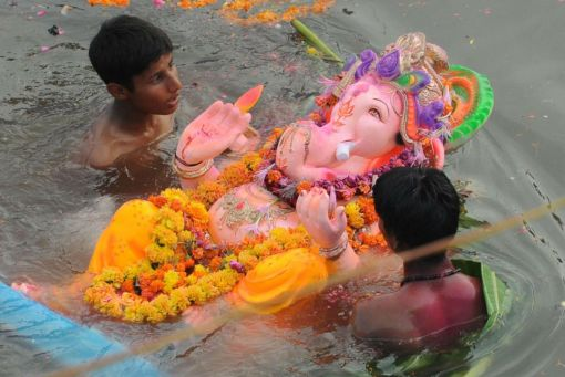 Indian Hindu devotees swim with an idol of Lord Ganesha in an artificial pond, dug for the ongoing Ganesh Chathurthi festival to help control pollution and waste, along the banks of the Sabarmati river in Ahmedabad. Hindu devotees bring home idols of Lord Ganesha during the 'Ganesh Chaturthi' in order to invoke his blessings for wisdom and prosperity, during the eleven day long festival which culminates with the immersion of the idols. (Sam PANTHAKY/AFP/Getty Images)