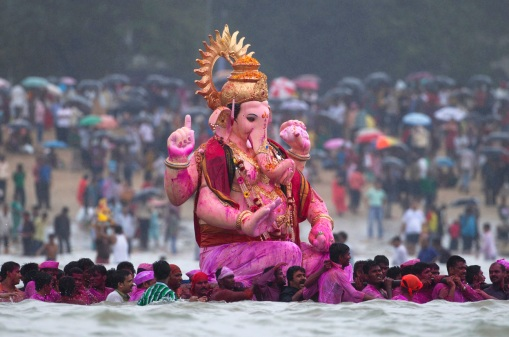"""Devotees carry an idol of Hindu elephant god Ganesh, the deity of prosperity, into the water from Girgaum Chowpatty beach before immersing it in the waters of the Arabian Sea on the last day of the Ganesh Chaturthi festival in Mumbai, on September 11, 2011. Idols are taken through the streets in a procession accompanied by dancing and singing, to be immersed in a river or the sea symbolizing a ritual send-off of his journey towards his abode in """"Kailash"""", while taking away with him the misfortunes of all mankind. (Reuters/Vivek Prakash)"""