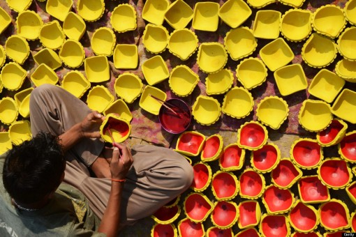 An Indian craftsman paints clay 'diyas' (earthen lamps) ahead of the Hindu festival of Diwali in Amritsar on October 29, 2013. Diwali, celebrated this year on November 3 marks the victory of good over evil and commemorates the time when Hindu God Lord Rama achieved victory over Ravana and returned to his Kingdom Ayodhya after 14 years of exile. AFP PHOTO/NARINDER NANU (Photo credit should read NARINDER NANU/AFP/Getty Images)