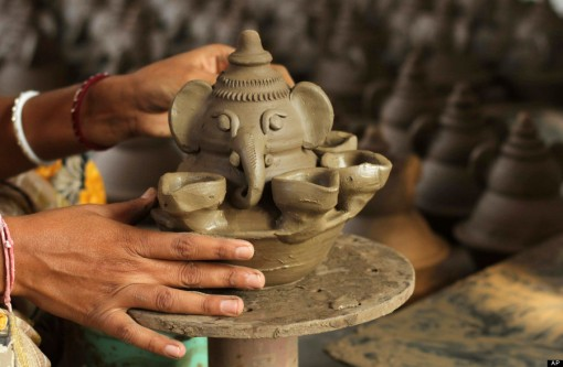 An Indian potter makes earthen lamps ahead of the Diwali festival in Ahmadabad, India, Thursday, Oct. 24, 2013. Diwali, the festival of lights will be celebrated on Nov. 3. (AP Photo/Ajit Solanki)
