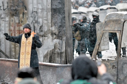 Jan. 22, 2014 – An Orthodox priest tries to stop a clash between protesters and the police in the center of Kiev, Ukraine. Anti-government street protests in Kiev turned deadly overnight, as opposition organizers announced that three demonstrators had been killed, one from a fall and two shot by police. Sergei Supinsky / AFP/Getty Images