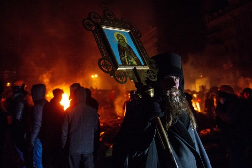 A priest holds an icon at a barricade of the anti-government demonstrators in the center of Kiev early on January 24, 2014. (SERGEI SUPINSKY/AFP/Getty Images)