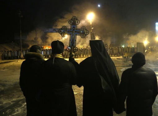 Orthodox priests pray as they stand between pro-European Union activists and police lines in central Kiev, Ukraine, early Friday, Jan. 24, 2014. (AP Photo/Sergei Grits)