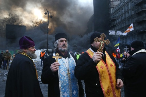 Priests of different faiths pray during clashes with police in central Kiev, Ukraine, Thursday, Jan. 23, 2014. (AP Photo/Sergei Grits)