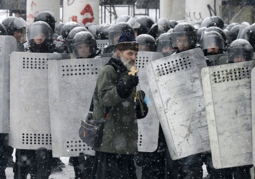 An Orthodox priest prays in front of police officers as they block a street after clashes in central Kiev, Ukraine, Wednesday, Jan. 22, 2014. (AP Photo/Efrem Lukatsky)