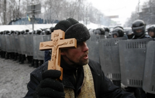 An Orthodox priest prays in front police officers as they block a street after clashes in central Kiev, Ukraine, Wednesday, Jan. 22, 2014. (AP Photo/Darko Vojinovic)