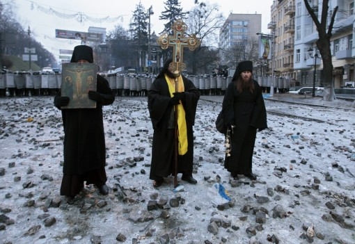 Orthodox priests pray as they stand between pro-European Union activists and police lines in central Kiev, Ukraine, Tuesday, Jan. 21, 2014. (AP Photo/Sergei Chuzavkov)