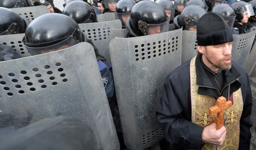 An Orthodox priest holds a cross in front of riot policemen standing guard in front of the parliament's building in Kiev on January 14, 2014, as Ukrainian veterans and invalids of Chernobyl's nuclear disaster try to give their demandings to the parliamentary leadership. (SERGEI SUPINSKY/AFP/Getty Images)