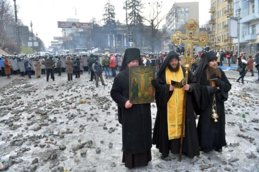"Three Ukrainian priest/monks from Kiev stood between protesters and soldiers last week, refusing to take sides and preserving peace. It is one of many such encounters between what The Guardian called ""steel-nerved priests"" and increasingly violent people on both sides. Photo source: Unknown; via Twitter."