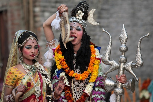 Indian Hindu devotees dressed as Hindu god Lord Shiva (R), seen holding a snake to his mouth, and Mata Parvati (L) participate in a procession on the eve of the Shivaratri festival in Jammu on February 26, 2014. (STRDEL/AFP/Getty Images)