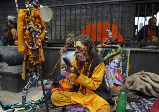 A Hindu Sadhu (holy man) paints coloured paste onto his face during the Maha Shivaratri festival at the Pashupatinath temple in Kathmandu on February 27, 2014. (PRAKASH MATHEMA/AFP/Getty Images)