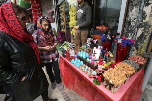 Iranian women shop for Noruz, the Persian New Year, at a market in Tehran on 19 March 2014. Iranians are preparing to celebrate Noruz, an ancient Zoroastrian feast starting 21 March, by buying flowers, green plants and goldfish. Noruz is calculated according to a solar calendar, this year marking 1393. AFP PHOTO/ATTA KENARE (Photo credit should read ATTA KENARE/AFP/Getty Images)
