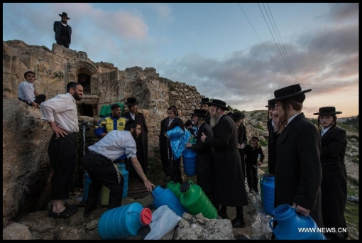 "Ultra-Orthodox Jews collect spring water during the sunset for the traditional Jewish rite of ""Mayim Shelanu"" (water which has ""slept"") outside Jerusalem, on April 3, 2014. Using this water they prepare matzo for the upcoming Jewish holiday of Passover, which begins on sunset of April 14 this year. (Xinhua/Li Rui)"
