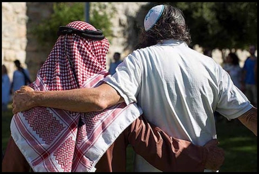 An Arab guy named Haj Ibrahim Ahmad Abu el-Hawa, and an unnamed Jewish guy in a knitted yarmulke hugging each other in front of the Old City walls of Jerusalem, during an event called The Big Hug, on June 24, 2013. Photo by Sarah Schuman/FLASH90