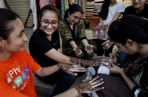 A Pakistani beautician paints hands of customers with henna ahead of the Muslim Eid al-Fitr holiday, ending the fasting month of Ramadan, in Karachi, Pakistan, on Sunday, July 27, 2014. (AP Photo/Fareed Khan)