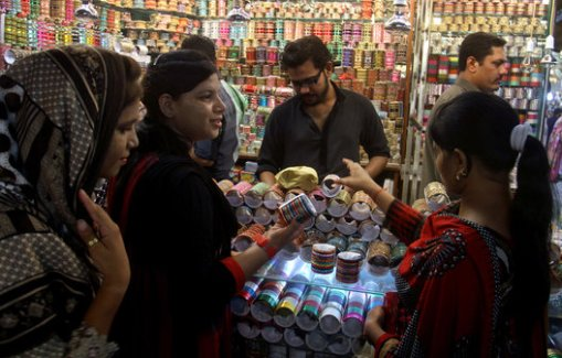 Pakistani girls buy traditional bangles at a market ahead of the Muslim Eid al-Fitr holiday, ending the fasting month of Ramadan, in Lahore, Pakistan, on Sunday, July 27, 2014. (AP Photo/K.M. Chaudary)