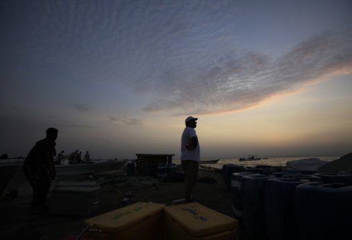 Bahraini fishermen look at the sky where a slim crescent moon should be visible to indicate the end of the Islamic holy month of Ramadan, in Malkiya village, Bahrain, Sunday, July 27, 2014. Bahrain and several other Gulf countries announced Eid will begin on Monday. (AP Photo/Hasan Jamali)