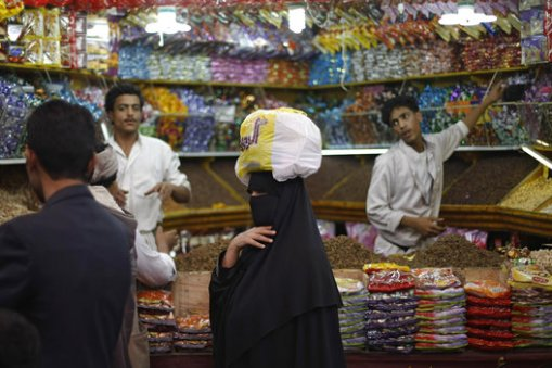A Yemeni woman, center, shops in preparation for the upcoming Eid al-Fitr festival, at a market in the old city of Sanaa, Yemen, Sunday, July 27, 2014. (AP Photo/Hani Mohammed)