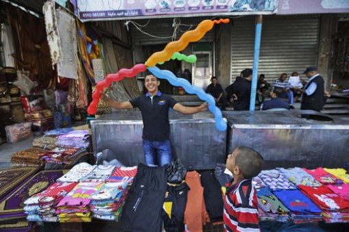 A Palestinian vendor plays with balloons at the market in the Jebaliya refugee camp, northern Gaza Strip, Sunday, July 27, 2014. During normal times, families in Gaza would be busy now with preparations for Eid al-Fitr, the three-day holiday marking the end of the Muslim fasting month of Ramadan. Traditionally, children get new clothes, shoes and haircuts, and families visit each other. In the outdoor market, vendors set up stands with clothes and shoes, but said business was slow. (AP Photo/Lefteris Pitarakis)