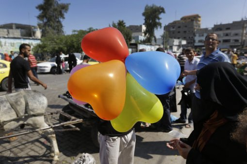A Palestinian vendor offers balloons for sale at the market in the Jebaliya refugee camp, northern Gaza Strip, Sunday, July 27, 2014. During normal times, families in Gaza would be busy now with preparations for Eid al-Fitr, the three-day holiday marking the end of the Muslim fasting month of Ramadan. Traditionally, children get new clothes, shoes and haircuts, and families visit each other. In the outdoor market, vendors set up stands with clothes and shoes, but said business was slow. (AP Photo/Lefteris Pitarakis)
