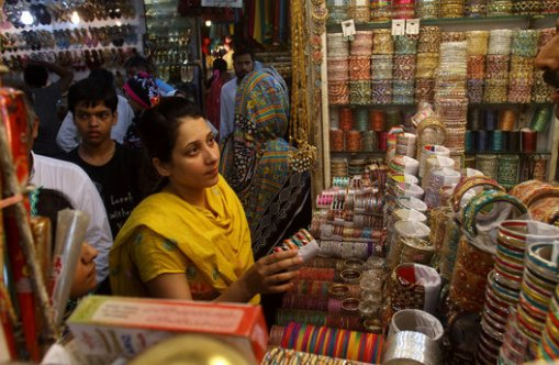 A Pakistani woman browses traditional bangles at a market ahead of the Muslim Eid al-Fitr holiday, ending the fasting month of Ramadan, in Lahore, Pakistan, on Sunday, July 27, 2014. (AP Photo/K.M. Chaudary)