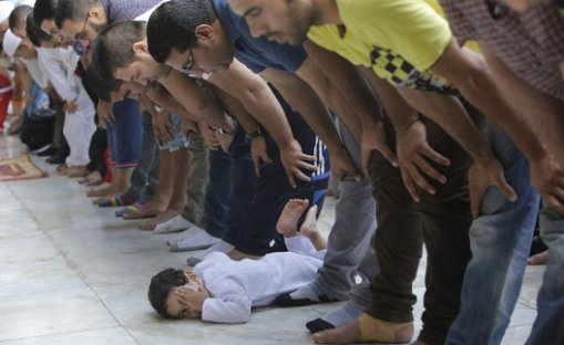 An Egyptian child plays as Muslims pray Eid al-Fitr prayers, marking the end of the Muslim holy fasting month of Ramadan at Al-Azhar mosque, the highest Islamic Sunni institution, in Cairo, Egypt, Monday, July 28, 2014. (AP Photo/Amr Nabil)