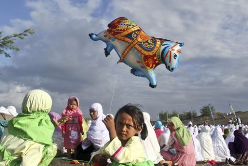 An Indonesian girl holds a balloon during Eid al-Fitr prayer that marks the end of the holy fasting month of Ramadan on Parang Kusumo Beach in Yogyakarta, Indonesia, Monday, July 28, 2014. (AP Photo/Slamet Riyadi)