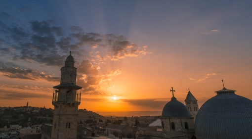 The sun rises over the Mount of Olives, framed between the Al-Khanqah al-Salahiyya Mosque on the left and the Church of the Holy Sepulchre on the right.