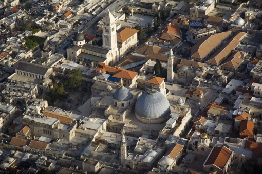The grey domes of the Church of the Holy Sepulchre (in the foreground) mark the place where many Christians believe Jesus was crucified and buried.